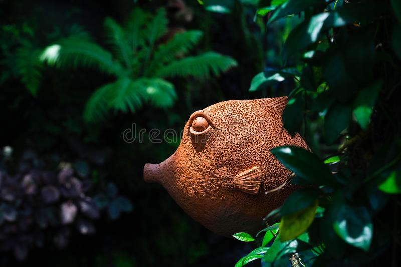 Decorative cute clay fish statue decorated in the tropical green garden royalty free stock image