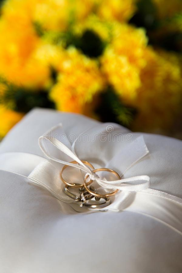 Decorative design for the wedding. Wedding rings and hearts on a cushion on a background of flowers royalty free stock photo