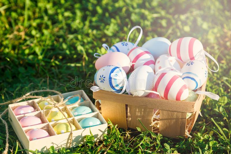 Decorative eggs in boxes on green spring grass under sunlight. Happy Easter! Egg hunt, decoration for Easter, spring stock photography