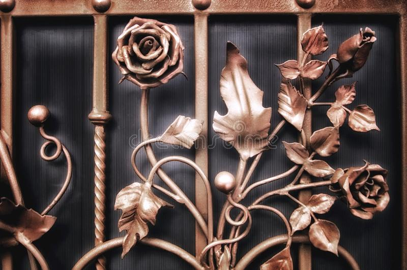 Decorative elements of the fence in the form of metallic flowers stock image