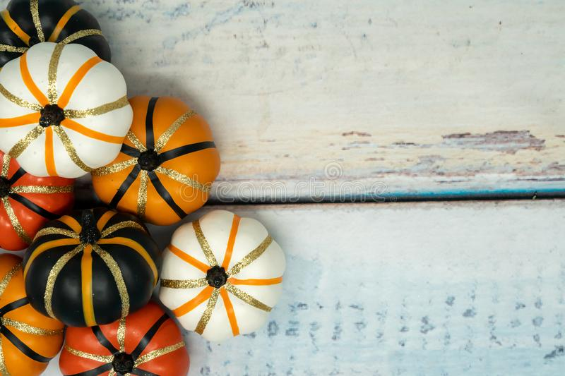 Decorative fake pumpkins white, orange and black with gold glitter details arranged on a blue wooden background. stock photography