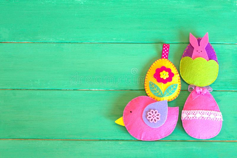 Decorative felt eggs and bird on green wooden background with copy space stock photo