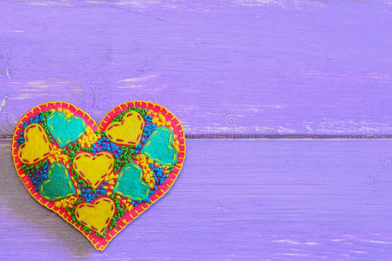 Decorative felt heart for Valentines Day. Embroidered heart ornament isolated on purple wooden background with copy space for text royalty free stock photo