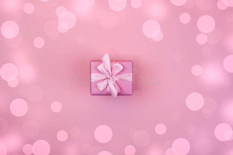 Decorative festive gift box with pink color on pink background. Flat flat top view stock photos