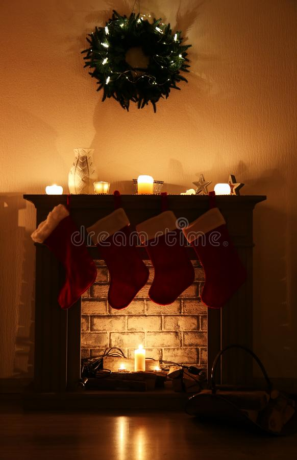 Decorative fireplace with Christmas stockings and fir wreath hanging on wall in living room stock photos