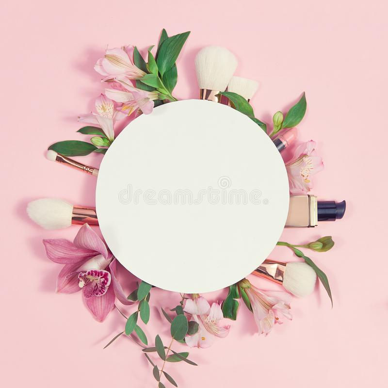 Decorative flat lay composition with makeup products, cosmetics and flowers. Flat lay, top view on pink background. Copytext royalty free stock photography