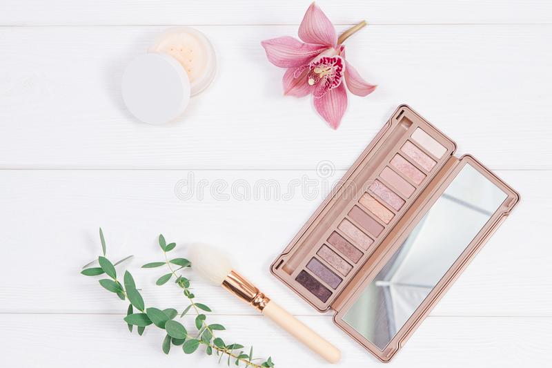 Decorative flat lay composition with makeup products, cosmetics and flowers. Flat lay, top view on wooden background. Copytext royalty free stock images
