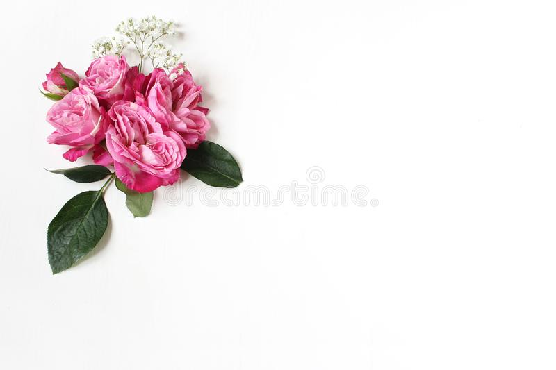 Decorative floral composition with pink roses, green leaves and and baby`s breath Gypsophila flowers on white table royalty free stock images