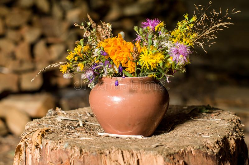 Decorative flowerpot made of wild flowers. Flowerpot with flowers in the barn. Front view royalty free stock photography