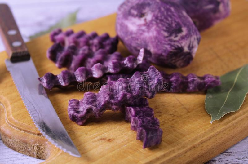 Wavy slices of purple potatoes. Decorative food design. Next to the knife for cutting and bay leaves, spices. Decorative food design stock images