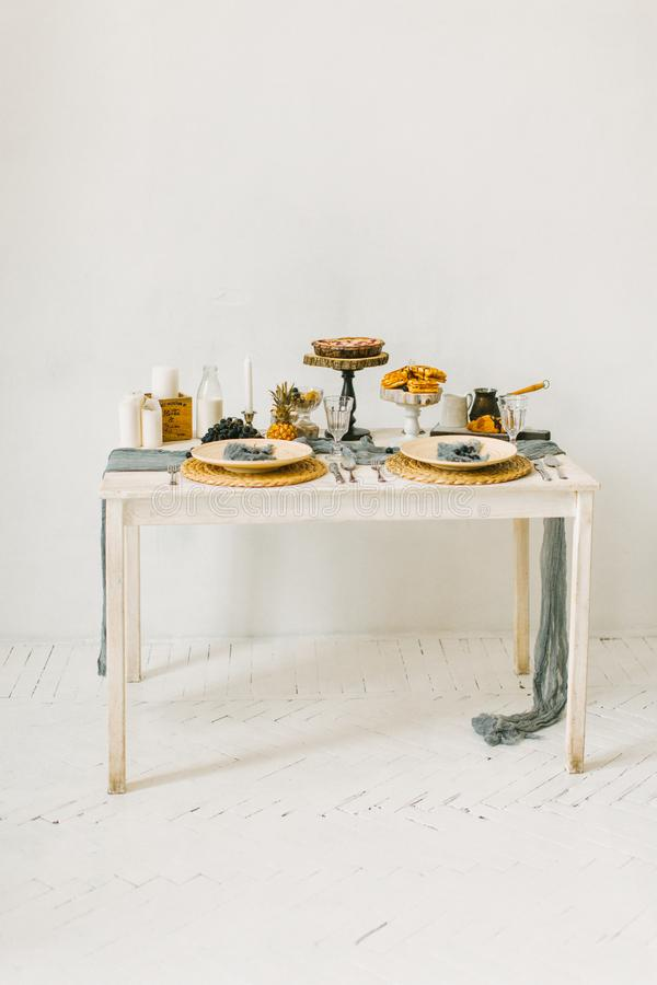 Decorative food serving on the white table in white room. Grey, yellow and white color scheme royalty free stock images