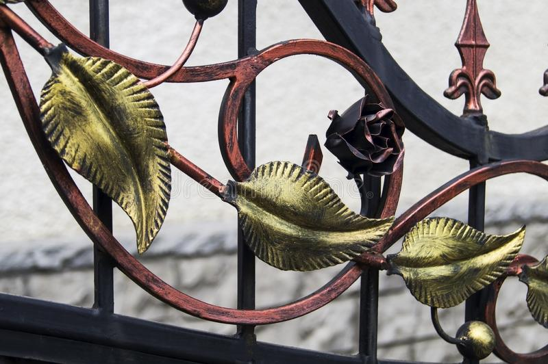 Decorative forged leaves made of iron on a metal fence royalty free stock photo