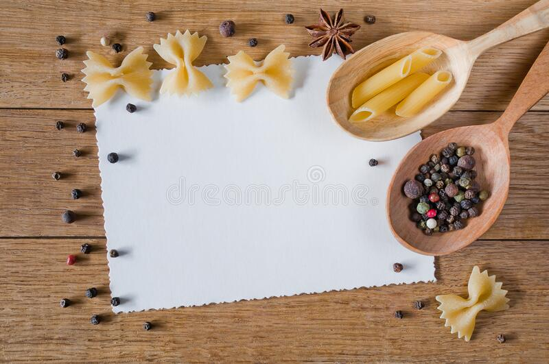 Decorative frame made of cardboard, pasta and peppercorns on a wooden table royalty free stock images