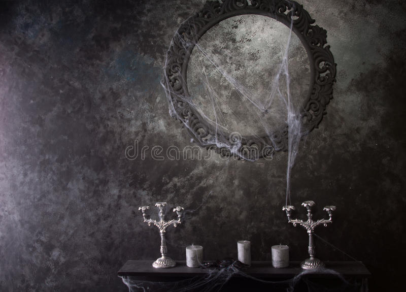 Decorative Frame and Mantle Covered in Cobwebs. Decorative Round Frame Above Candles and Candelabras on Eerie Cobweb Covered Mantle in Haunted House Setting royalty free stock image