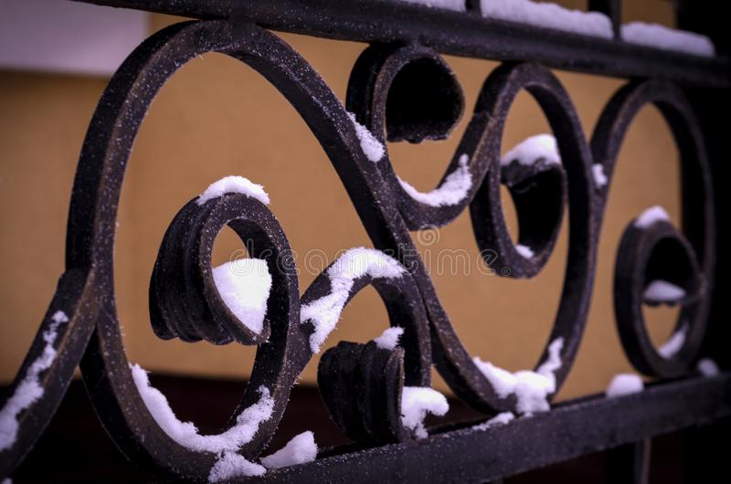 Decorative framing of a metal fence with forged elements stock image