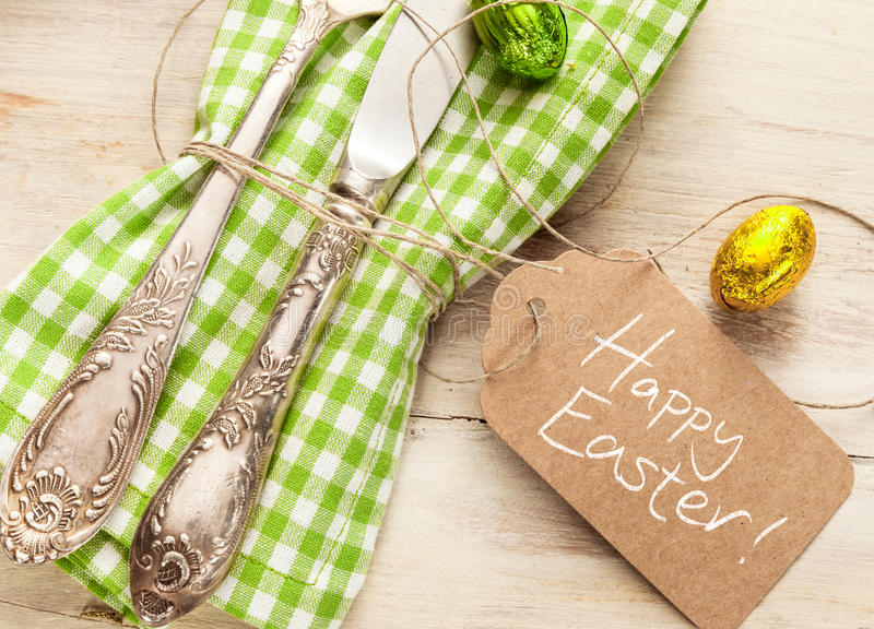 Decorative fresh spring Easter table setting. With a vintage silver knife and fork over a white and green checked napkin with a Happy Easter greeting on a gift royalty free stock photography