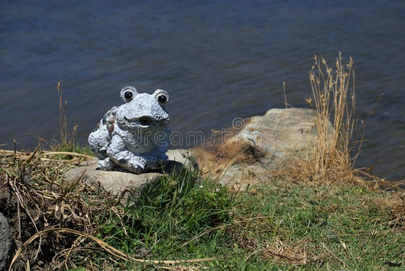 Decorative garden frog near pond stock photo