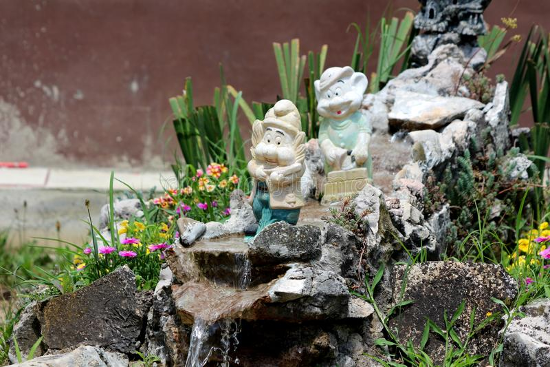 Decorative garden gnomes with faded color standing on top of improvised garden waterfall in suburban family house front yard. Surrounded with small flowers and royalty free stock photo