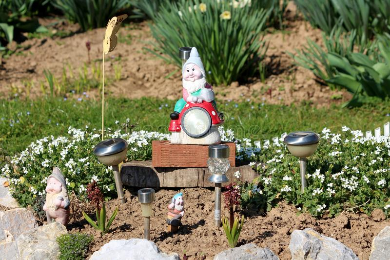 Decorative garden gnomes in various shapes and sizes surrounded with solar lights rocks and small flowers in local garden. On warm sunny spring day stock image