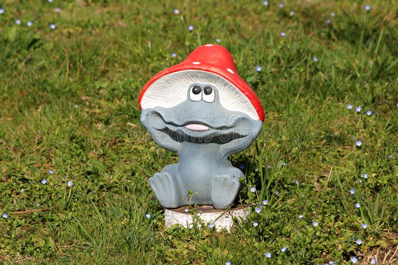 Decorative garden ornament shaped like funny smiling children toy frog with bright red mushroom hat surrounded with uncut grass royalty free stock photos