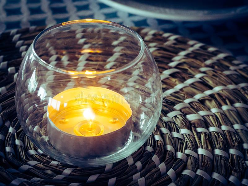 Decorative glass with a burning candle inside stock image