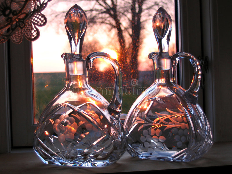 Decorative glass carafes bottles. By the window royalty free stock images