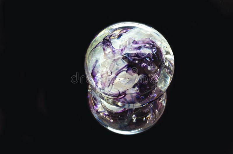 Decorative Glass Sphere and Reflection Against Black. Textured glass paperweight and reflection isolated against black royalty free stock photography