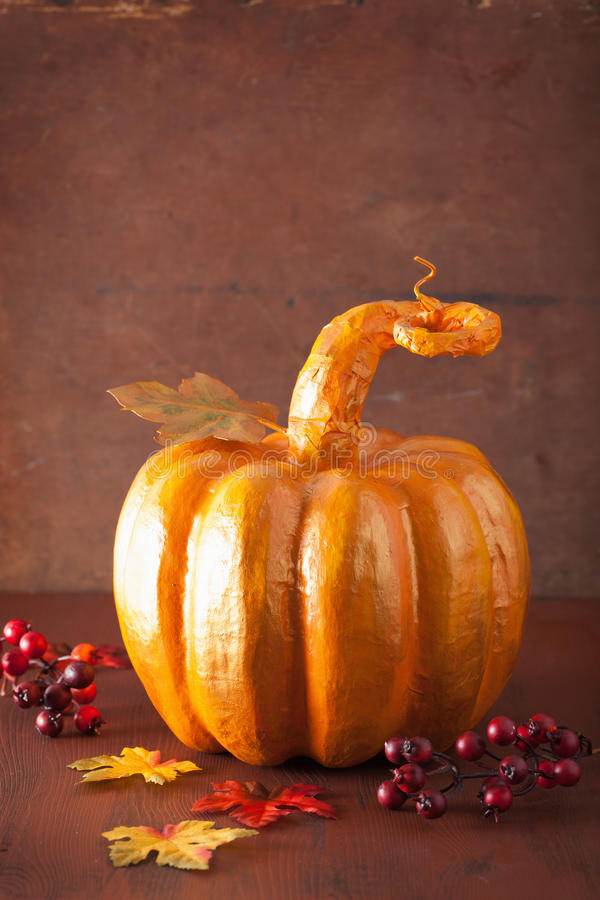 Decorative golden papier-mache pumpkin and autumn leaves for hal. Loween thanksgiving stock image