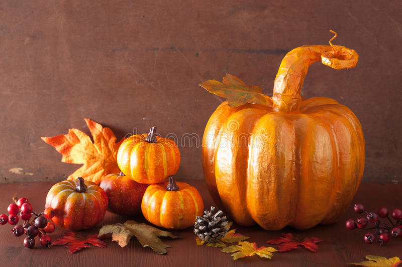 Decorative golden papier-mache pumpkin and autumn leaves for hal. Loween thanksgiving royalty free stock images