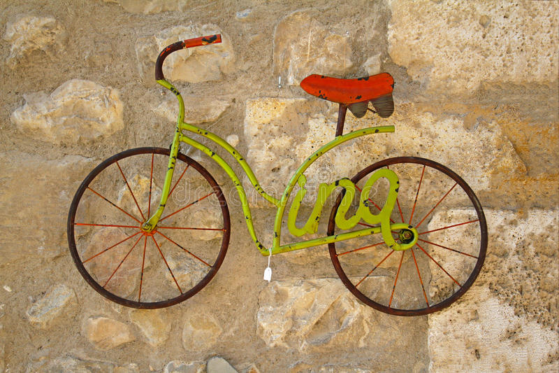 A decorative green bicycle model hanging on stone wall for sale in the market of Besalu Catalonia, Spain stock photos
