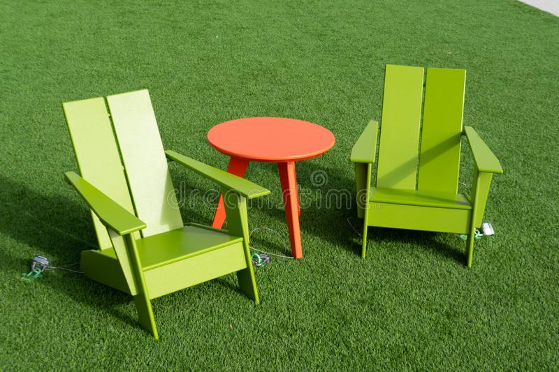 Decorative wooden chairs and table on the bright green lawn royalty free stock photography
