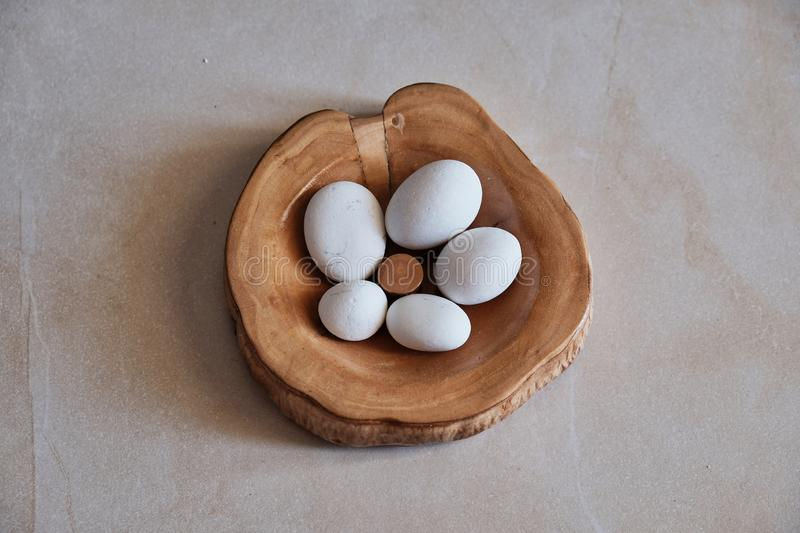Sea Smoothed White Marble Pebbles in Wooden Bowl. Decorative handicrafts; small white marble pebbles smoothed and shaped by constant tumbling in the ocean royalty free stock photos