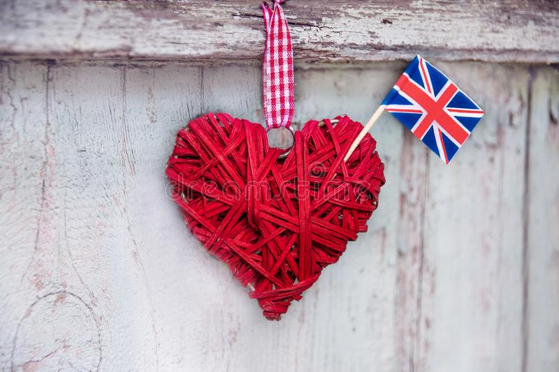 Decorative heart made of straw with the flag of the United Kingdom on the background of a wooden textured fence royalty free stock image
