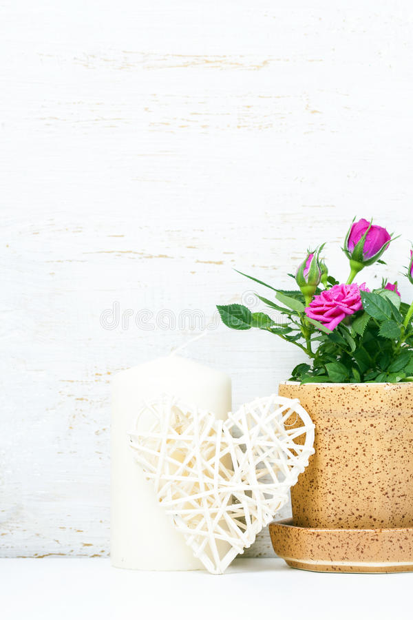 Decorative heart, pink roses and candles on white wooden background. Selective focus. Place for text. royalty free stock photography