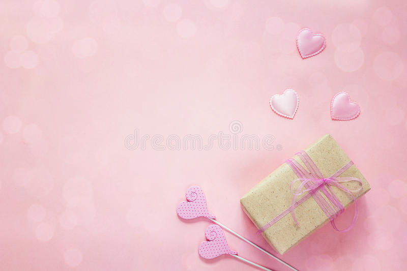 Decorative hearts and gift box on pink background. Top view with royalty free stock image