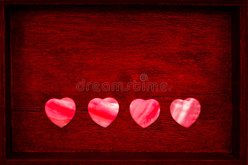 Decorative hearts made of shells on vintage wooden background stock photography