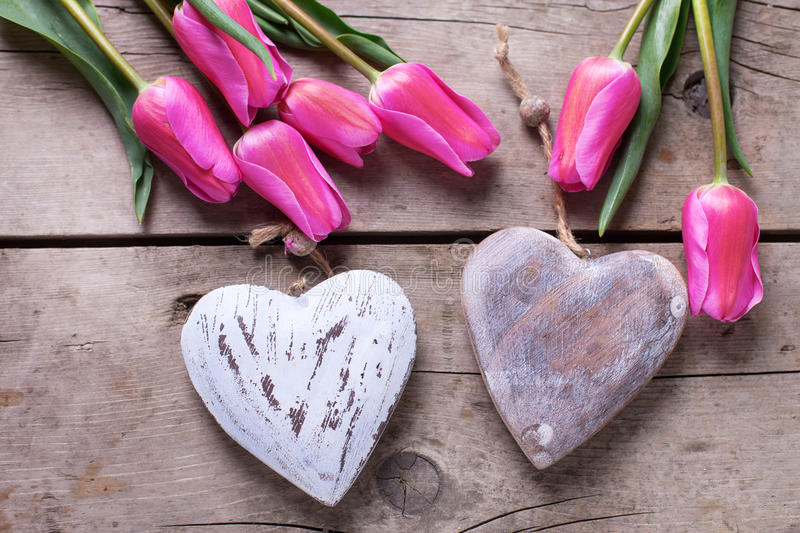 Decorative hearts and pink spring tulips on vintage wooden back. Ground. Selective focus. Flat lay royalty free stock photos