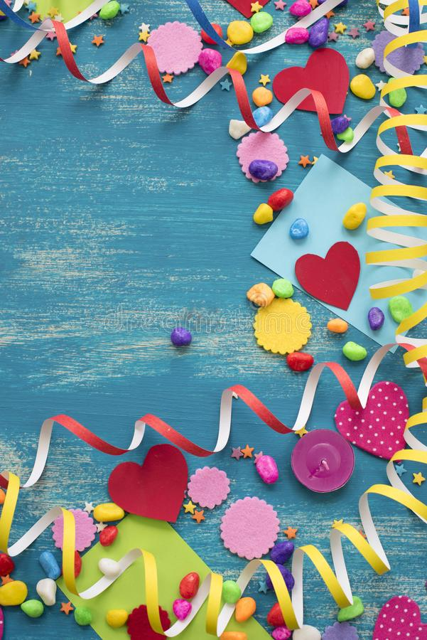 Decorative holiday background with streamers confetti candy hearts decor. Blue shabby wooden top view background flat lay royalty free stock images