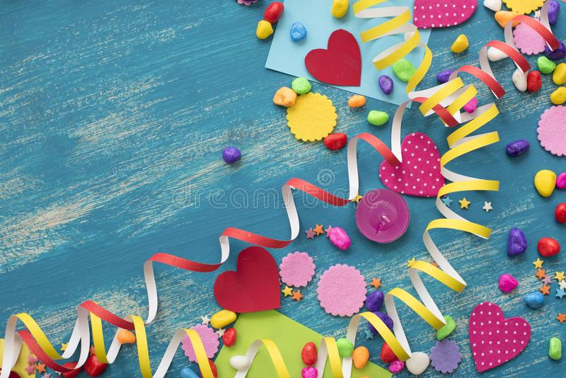 Decorative holiday background with streamers confetti candy hearts decor. Blue shabby wooden top view background flat lay royalty free stock photos