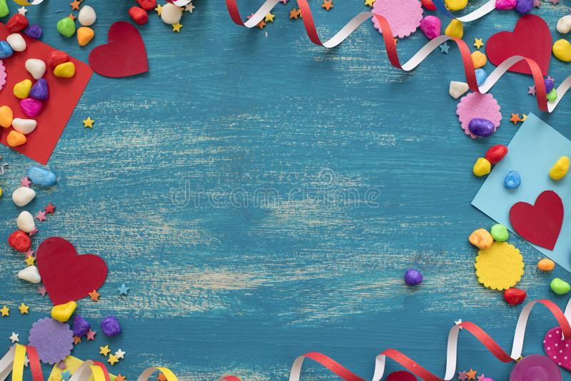 Decorative holiday background with streamers confetti candy hearts decor. Blue shabby wooden top view background flat lay stock photos
