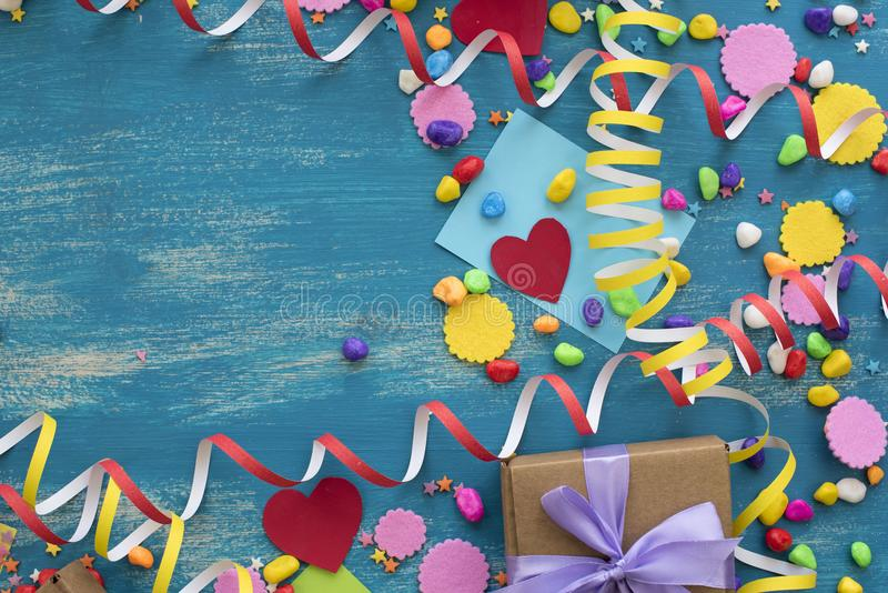 Decorative holiday background with streamers confetti candy hearts decor. Blue shabby wooden top view background flat lay royalty free stock photography