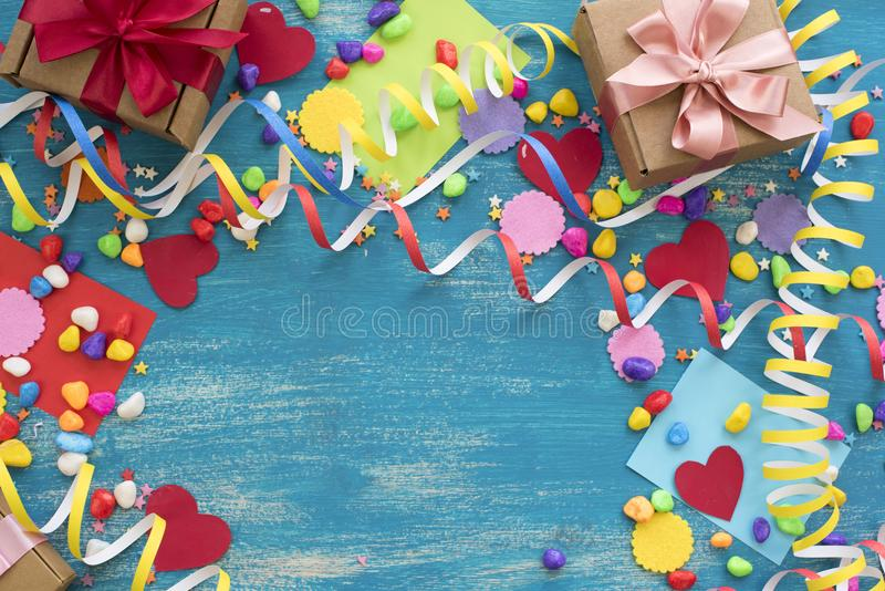 Decorative holiday background with streamers confetti candy hearts decor. Blue shabby wooden top view background flat lay stock photo