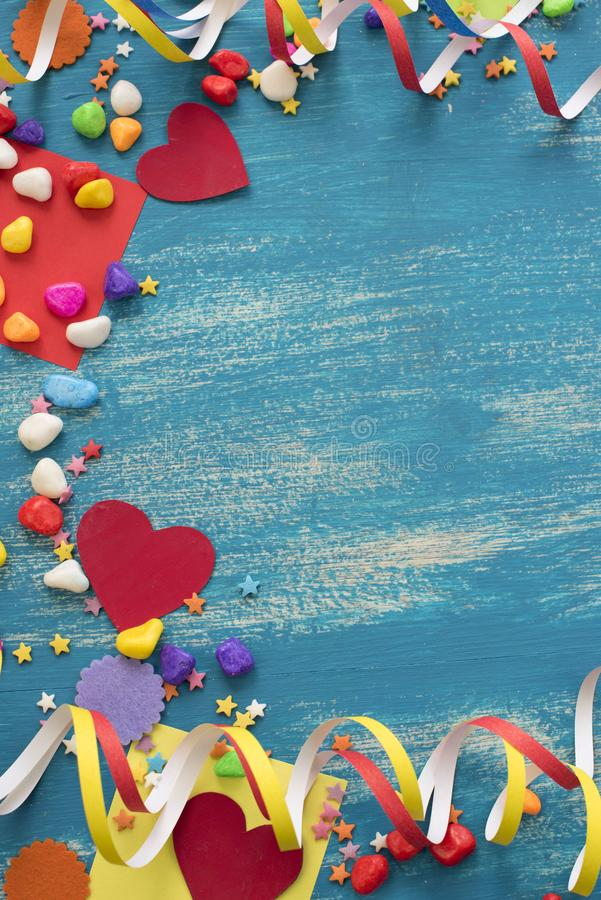 Decorative holiday background with streamers confetti candy hearts decor. Blue shabby wooden top view background flat lay royalty free stock photo