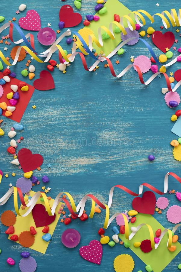Decorative holiday background with streamers confetti candy hearts decor. Blue shabby wooden top view background flat lay stock photography