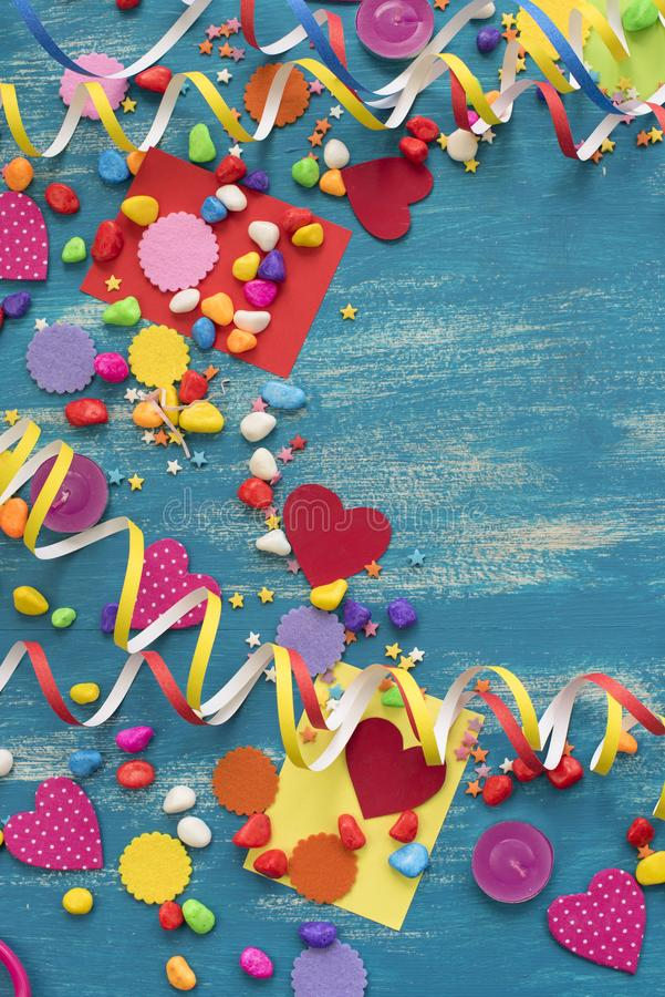 Decorative holiday background with streamers confetti candy hearts decor. Blue shabby wooden top view background flat lay stock images