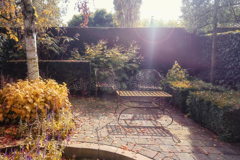 Decorative iron garden chairs and table in the autumn sun in the royalty free stock photography