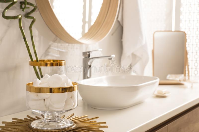 Decorative jar with cotton pads on modern countertop in bathroom. Interior stock photo