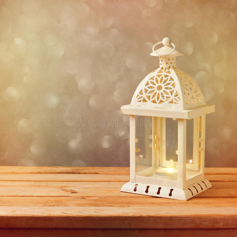 Decorative lantern with glowing candle on wooden table with copy space. Christmas celebration stock photography