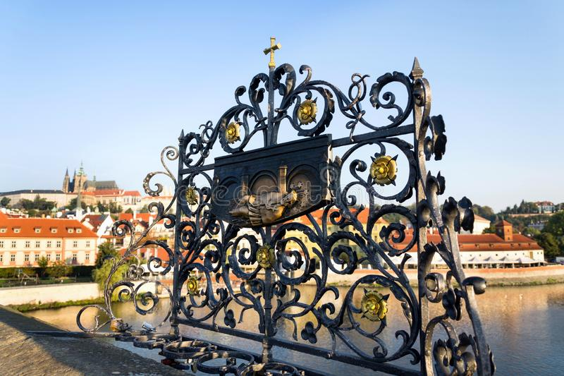 Decorative lattice with John of Nepomuk bronze statue on Charles Bridge, Prague, Czech Republic, sunny day. Clear sky royalty free stock photo