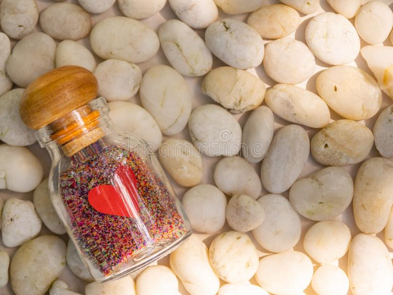A Decorative Love Glass Bottle with Colorful sand Inside on white stones background stock photos